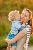 Woman and child outdoors at sunset. Boy kissing his mom. Happy women and child having fun outdoors.  Family lifestyle rural scene of mother and son in sunset Royalty Free Stock Image
