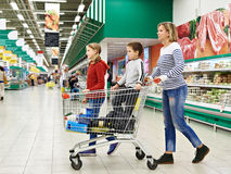 Happy women and children with cart shopping Royalty Free Stock Photos