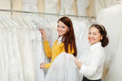Happy women chooses bridal clothes at wedding store. Royalty Free Stock Photography