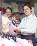Happy women  chooses wear at clothes shop. Focus on woman Royalty Free Stock Photos