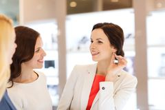 Happy women choosing earrings at jewelry store Stock Images
