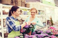 Happy women choosing flowers in greenhouse Stock Photography