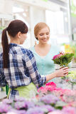 Happy women choosing flowers in greenhouse Royalty Free Stock Photography