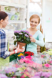 Happy women choosing flowers in greenhouse or shop Stock Images