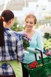 Happy women choosing flowers in greenhouse or shop Stock Photos