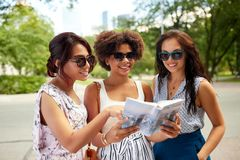 Happy women with city guide on street in summer stock photos