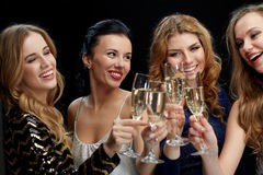 Happy women clinking champagne glasses over black Stock Photography