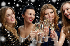 Happy women clinking champagne glasses over black Royalty Free Stock Images