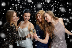 Happy women clinking champagne glasses over black. Celebration, friends, bachelorette party and holidays concept - happy women clinking champagne glasses and Royalty Free Stock Image