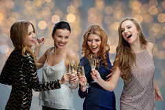 Happy women clinking champagne glasses over lights. Celebration, friends, bachelorette party and holidays concept - happy women clinking champagne glasses over Stock Images