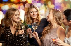 Happy women clinking glasses at night club stock photos