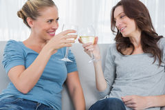 Happy women clinking their wine glasses while sitting on the sofa Royalty Free Stock Image