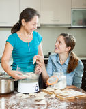 Happy  women cooking pies with electric steamer Stock Image