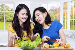 Happy women cooking salad in kitchen Royalty Free Stock Image