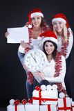 Three happy women in costume of Santa Claus with clock,and Chris. Happy women in costume of Santa Claus with clock, and Christmas shopping . isolated on black stock photos