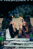 Happy women couple holding sparklers in a party Stock Photos