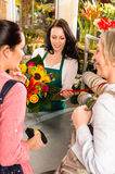 Happy women customers buying flowers sunflower bouquet Stock Images