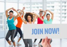 Happy women dancing in fitness studio with hand holding placard in foreground royalty free stock photography