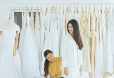 Happy woman designer making adjustment in fashion studio,Asian bride smling and trying on wedding dress. Happy women designer making adjustment in fashion studio royalty free stock images