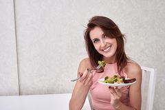 Happy women is on dieting time looking at broccoli on the fork. concept healthy food. Happy woman is on dieting time looking at broccoli on the fork Royalty Free Stock Image