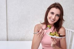 Happy women is on dieting time looking at broccoli on the fork. concept healthy food. Happy woman is on dieting time looking at broccoli on the fork Stock Photos