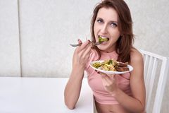 Happy women is on dieting time looking at broccoli on the fork. concept healthy food. Happy woman is on dieting time looking at broccoli on the fork Stock Image
