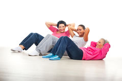 Happy women doing abs. Laughing happy women having fun and doing abs on floor over white background Stock Images