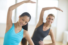 Happy Women Doing Stretching Exercise At Gym Royalty Free Stock Image