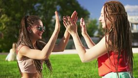 Happy women with dreads sitting on grass in summer park. Young friends talking and playing outdoors having fun. Mulatto stock footage