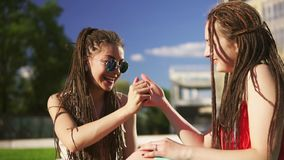 Happy women with dreads sitting on grass in summer park. Young friends talking and playing outdoors having fun stock footage