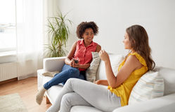 Happy women with drink talking gat home Royalty Free Stock Image