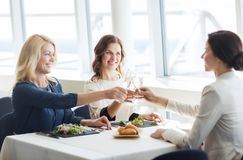 Happy women drinking champagne at restaurant Royalty Free Stock Image