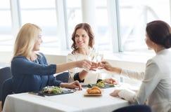 Happy women drinking champagne at restaurant Stock Photo