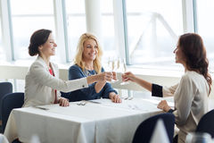 Happy women drinking champagne at restaurant Stock Photos
