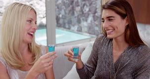 Happy women drinking shots. On the sofa stock video