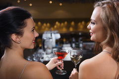 Happy women with drinks at night club bar Stock Image