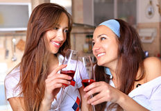 Happy women drinks wine. Happy women drinks red wine in the kitchen and talk about royalty free stock photo