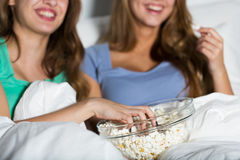 Happy women eating popcorn and watching tv at home. Friendship, people, pajama party, entertainment and junk food concept - close up of happy friends or teenage Stock Photo