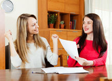 Happy women with financial documents. At table in home or office interior Stock Images