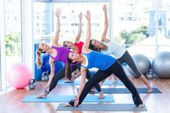 Happy women in fitness studio doing side stretch Stock Photography