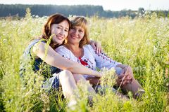 Happy women with flower relaxes in the grass with a flower. Royalty Free Stock Photography
