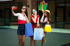 Happy women friends customers with shopping bags doing selfie. Pretty happy bright women female girls friends in colorful dresses, hats and high heels with royalty free stock photography