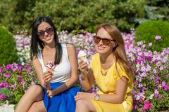Happy women friends eating ice cream. Happy young beautiful women friends eating ice cream Royalty Free Stock Images