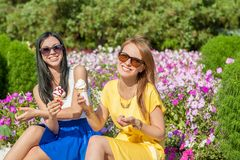 Happy women friends eating ice cream. Happy young beautiful women friends eating ice cream Stock Image