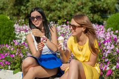 Happy women friends eating ice cream. Happy young beautiful women friends eating ice cream Royalty Free Stock Photo