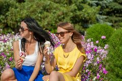 Happy women friends eating ice cream. Happy young beautiful women friends eating ice cream Royalty Free Stock Photos