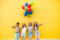 Happy women friends have fun with balloons. Picture of young happy women friends standing over yellow wall. Have fun with balloons Stock Images