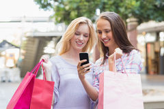 Happy women friends looking at smartphone Royalty Free Stock Image