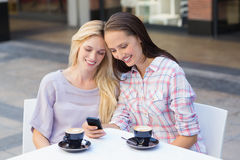 Happy women friends looking at smartphone Stock Photo