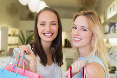 Happy women friends smiling at camera with shopping bags Royalty Free Stock Photo